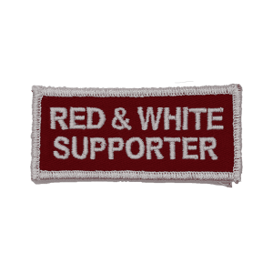 red and white supporter patch, white text, red background